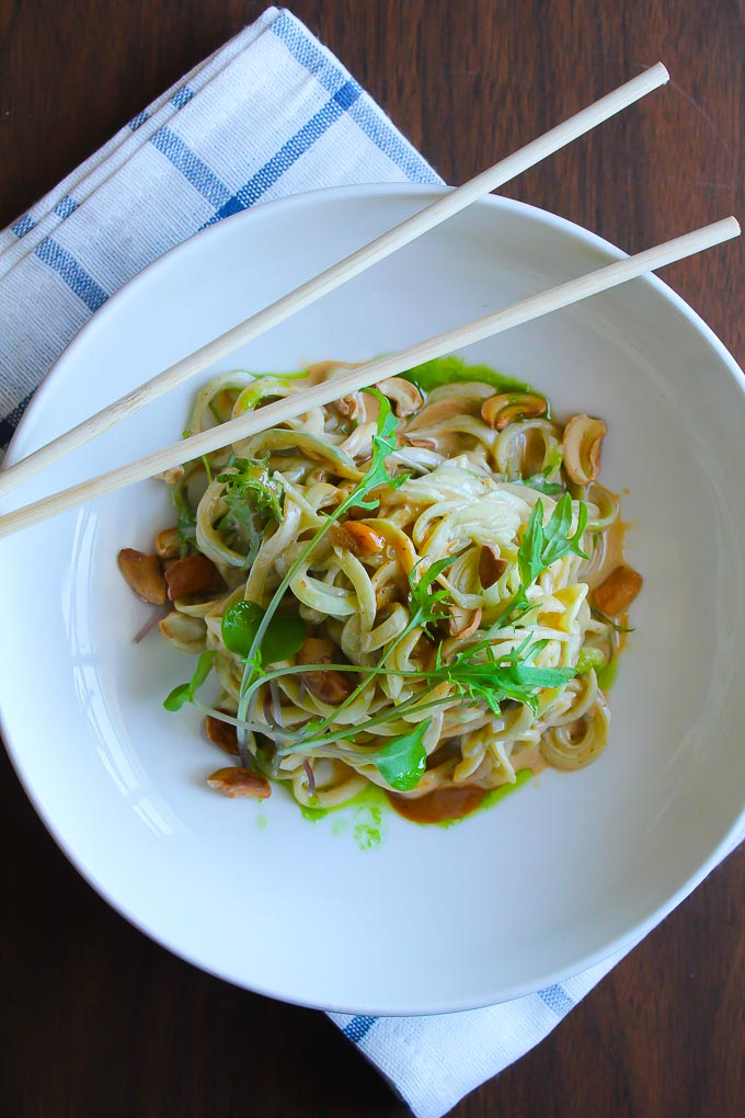 Raw vegan Asian cucumber noodles with a spicy tahini sauce , cashews, and baby kale